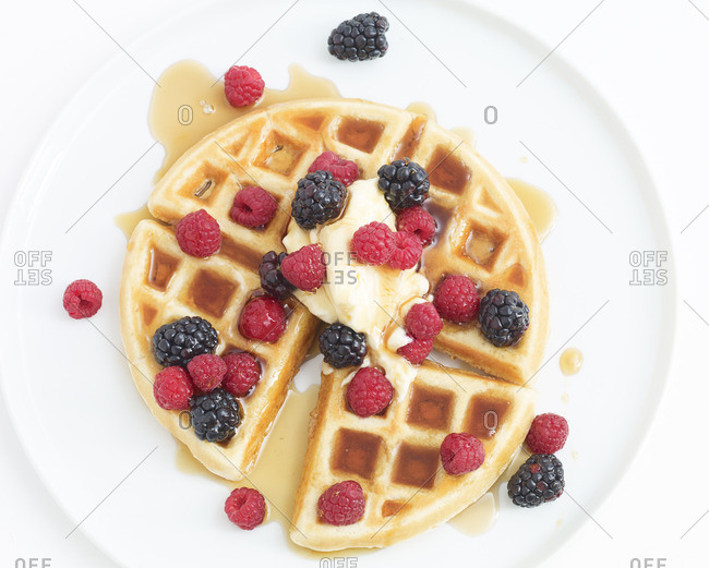 Belgian waffle served with butter, blackberries, raspberries, and syrup