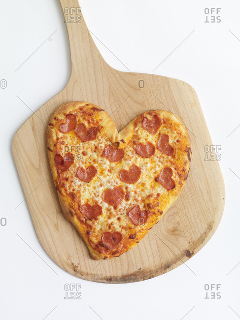 Heart shaped pepperoni pizza served on a wooden pizza peel