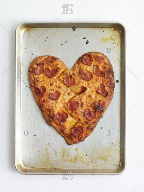 Heart shaped pepperoni pizza on a baking sheet