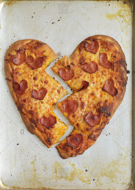 Heart shaped pepperoni pizza cut in two pieces