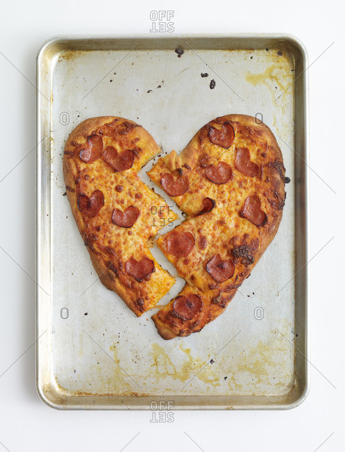 Heart shaped pepperoni pizza cut in two pieces on baking sheet
