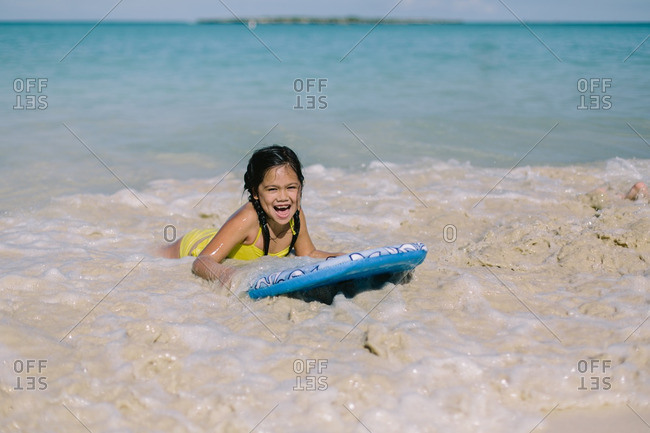 Young girl riding a boogie board in ocean