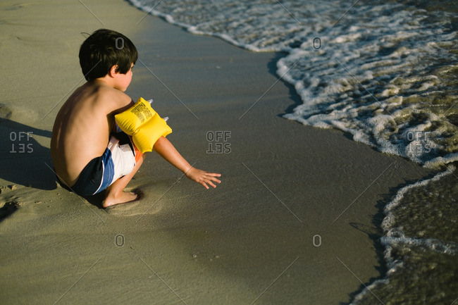 Young boy squatting on sand watching incoming waves