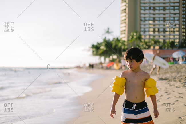 Young boy wearing water wings on at tropical beach resort