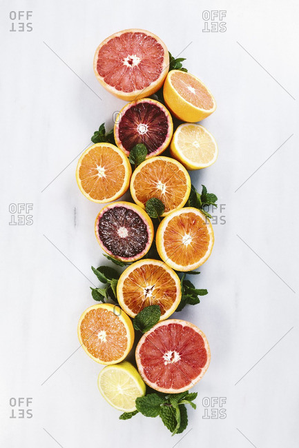 Citrus orange, grapefruit and mint display on marble.