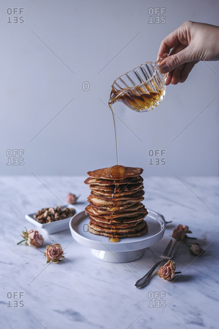 Woman pouring maple syrup over stack of pancakes