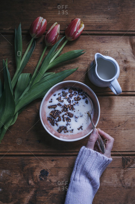 Woman eating cacao buckwheat granola with almond milk for breakfast