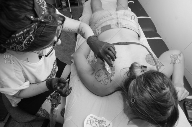 Stylish hipster tattoo artist tattooing a woman in her studio.
