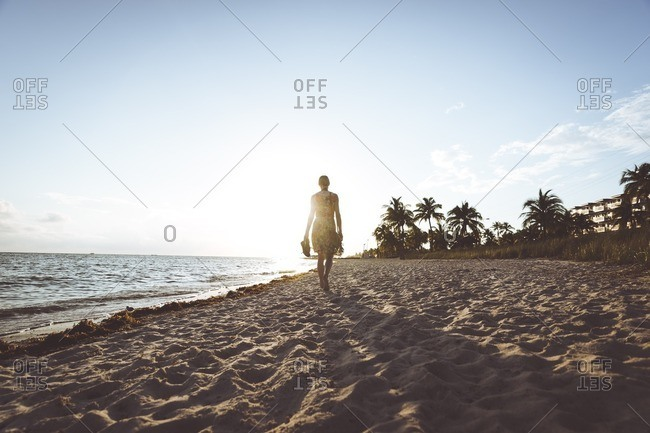 USA- Florida- Key West- woman walking on the beach at sunset