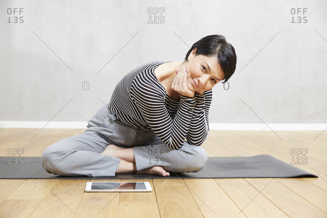 Smiling woman sitting on yoga mat with tablet