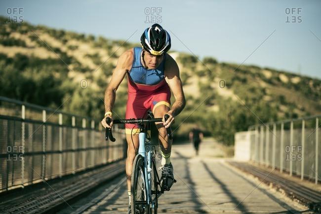 Athlete riding bicycle on a bridge