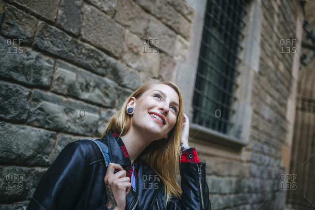 Spain- Barcelona- smiling young woman looking up