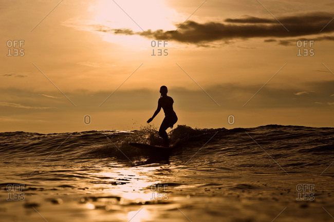 Indonesia- Bali- silhouette of woman surfing at sunset