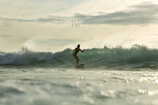 Indonesia- Bali- woman surfing at sunset