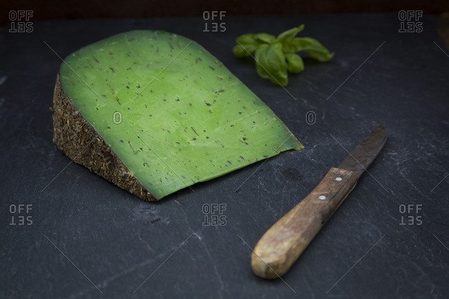 Piece of basil cheese- kitchen knife and basil leaves on slate
