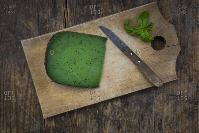 Piece of basil cheese- kitchen knife and basil leaves on wooden board
