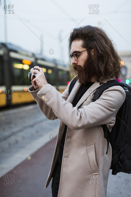 Stylish young man outdoors taking pictures in the city