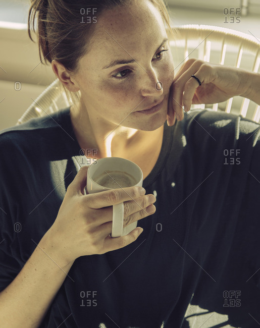 Pensive young woman sitting in a chair with coffee mug