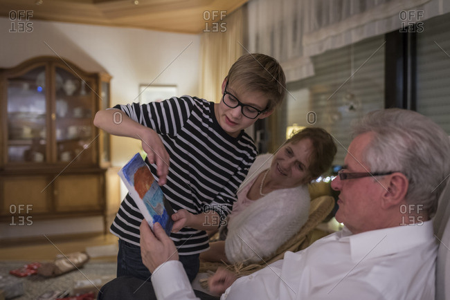 Gift giving at Christmas eve- boy showing present to grandparents