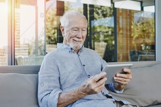 Senior man sitting on terrace reading e-book