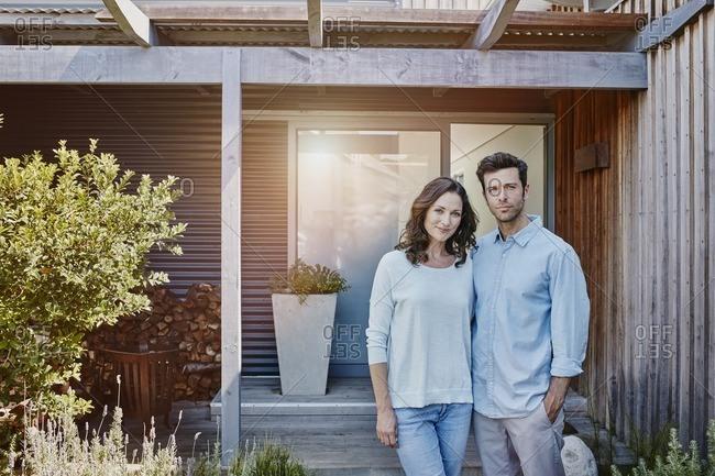 Couple standing in front of door of their home