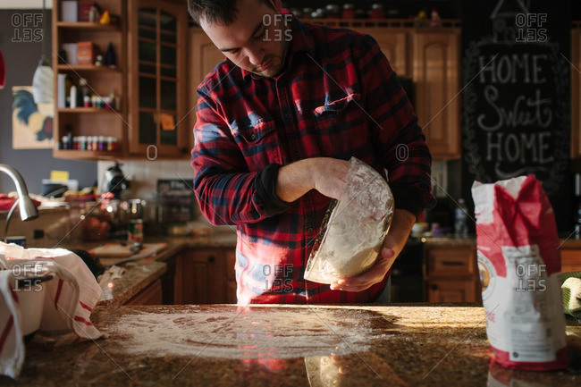 Man tipping bowl to put dough on floured counter