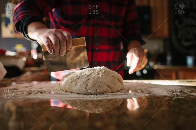 Man using a dough cutter to divide dough