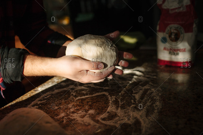 Man forming ball of dough with hands
