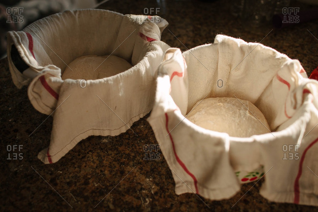 Balls of dough resting in bowls with towels
