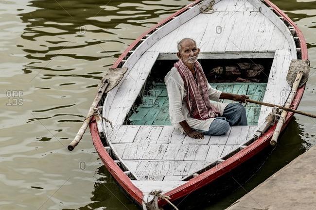Varanasi, India - July 7, 2016: Man in boat in the Ganges River