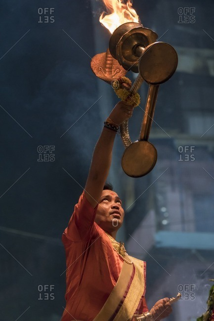 Varanasi, India - July 7, 2016: Man performing a ritual with fire during a Hindu Puja ceremony