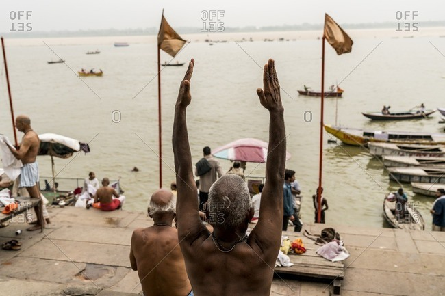 Varanasi, India - July 8, 2016: Hindu man with his hands raised in prayer at the Ganges River
