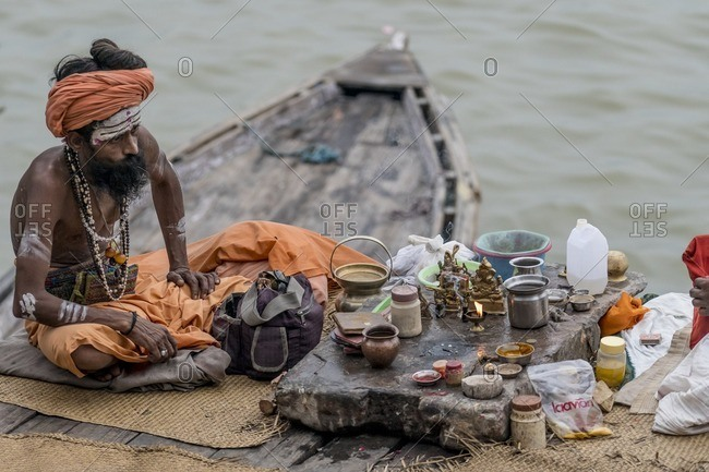 Varanasi, India - July 8, 2016: Hindu sadhu worshiping on boat in Ganges River
