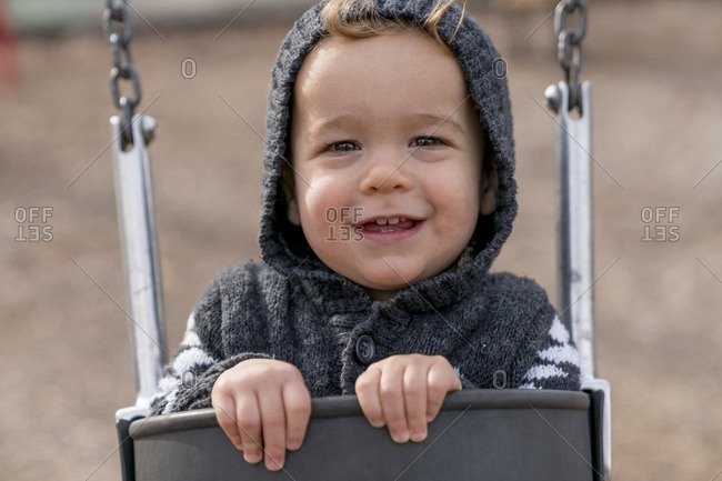 Close-up of baby boy riding in swing