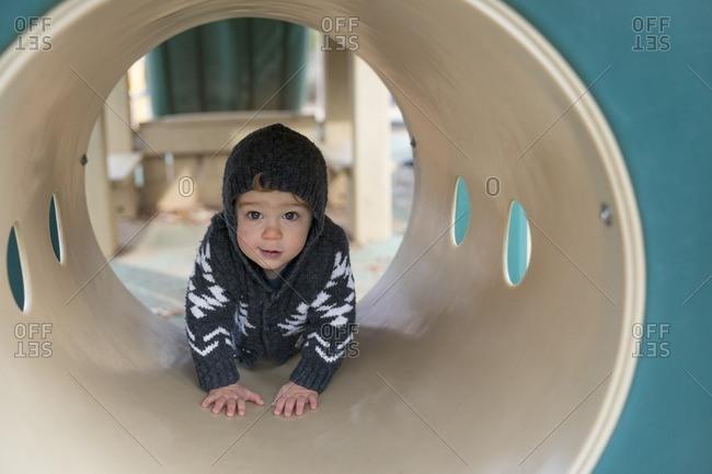 Toddler boy crawling through playground tunnel