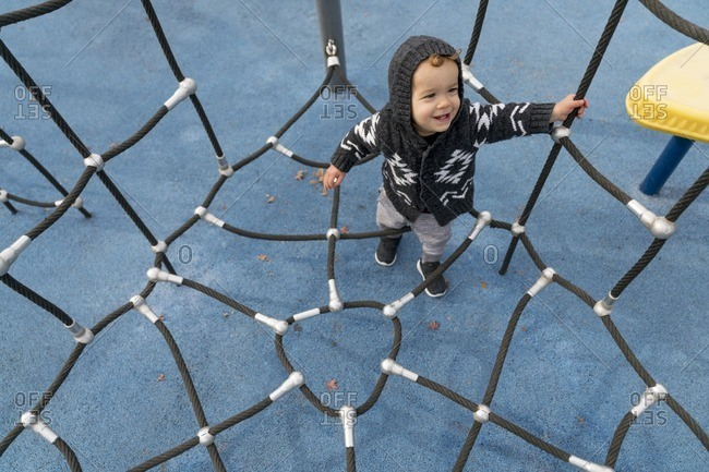 Toddler boy in climbing in playground net
