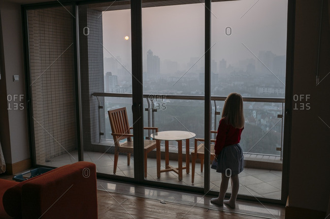 January 12, 2017 - Shanghai, China: Young girl looks out the window at a smog-filled sunrise
