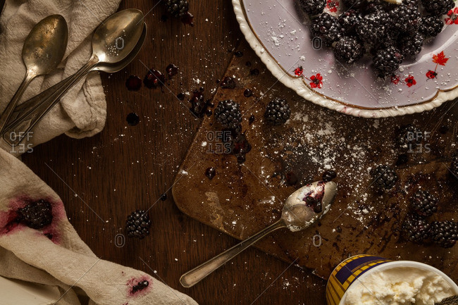 Arrangement of blackberries and container of ricotta cheese with spoons