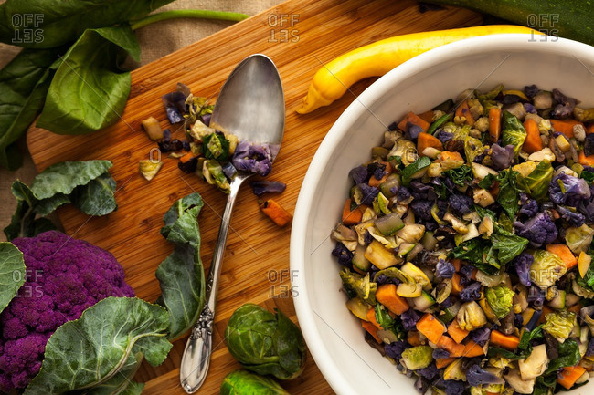 Bowl of colorful roasted vegetables on cutting board