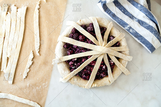 Overlapping strips of dough on a raspberry pie