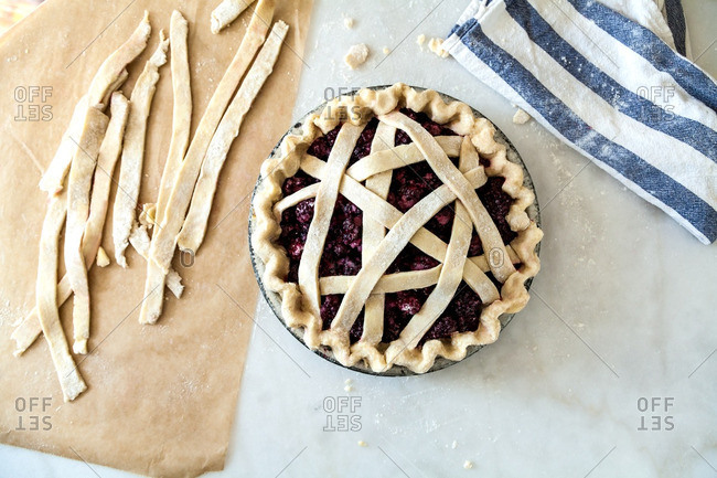 Criss-crossing strips of dough on a raspberry pie