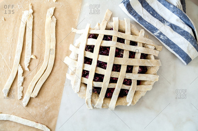 Strips of dough forming a grid on top of a raspberry pie