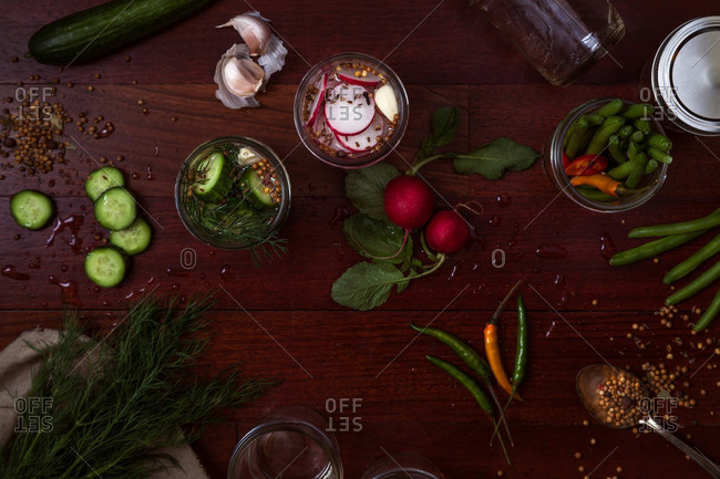 Overhead view of table with jars and vegetables for pickles