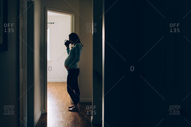 Pregnant woman in silhouette in hallway