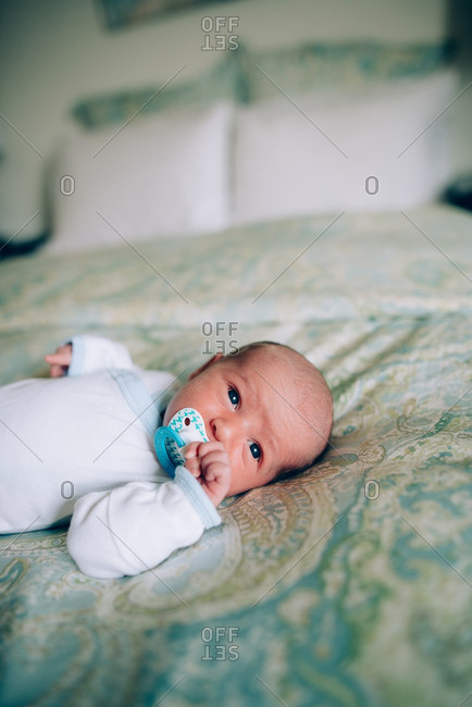 Newborn with pacifier on top of bed