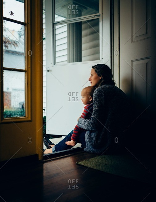 Woman sitting with baby in front door