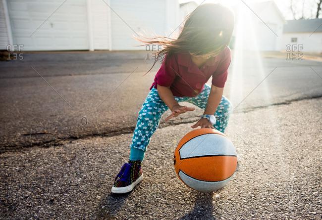 Girl dribbling basketball in driveway