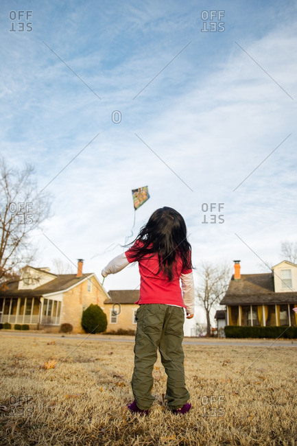 Girl flying kite in field