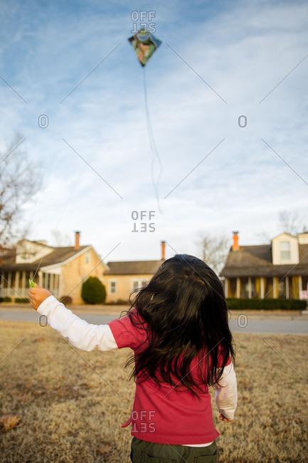 Girl flying kite in neighborhood