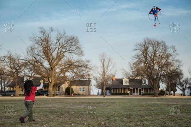 Girl flying kite in neighborhood park